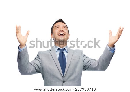 business, people and office concept - happy businessman in suit with raised hands laughing and looking up - stock photo