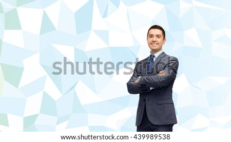 business, people and office concept - happy smiling businessman in dark grey suit over blue low poly texture background - stock photo