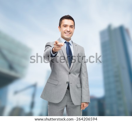 business, people and office concept - happy smiling businessman in suit pointing at you over city background - stock photo