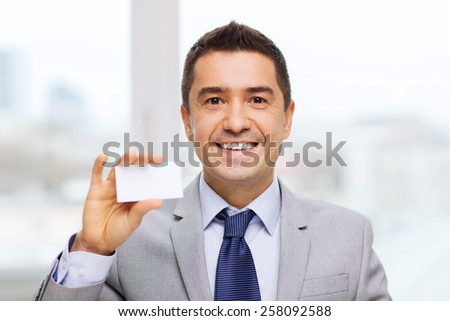 business, people and office concept - smiling businessman in suit showing blank white visiting card - stock photo