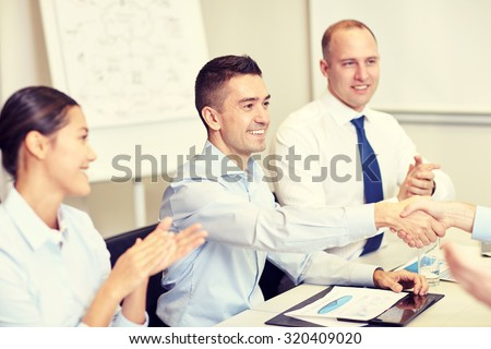 business, people and partnership concept - smiling business team shaking hands and applauding in office - stock photo