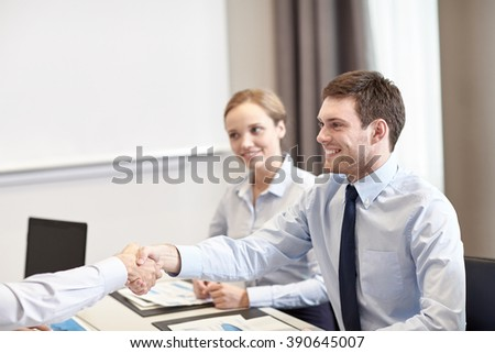 business, people and partnership concept - smiling business team shaking hands in office
