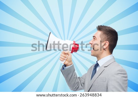 business, people and public announcement concept - happy businessman in suit speaking to megaphone over blue burst rays background - stock photo