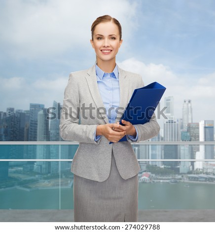 business, people and real estate concept - smiling young businesswoman holding folder over city background - stock photo