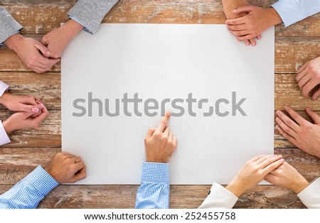 business, people and team work concept - close up of creative team sitting at table and pointing finger to blank paper in office - stock photo