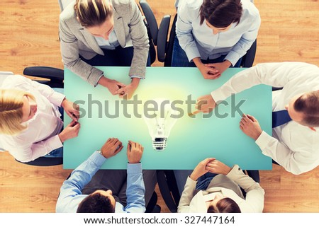 business, people and team work concept - close up of creative team sitting at table and pointing finger to lighting bulb in office - stock photo