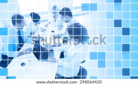 business, people and teamwork concept - business team with laptop computer and papers meeting in office over blue squared grid background - stock photo