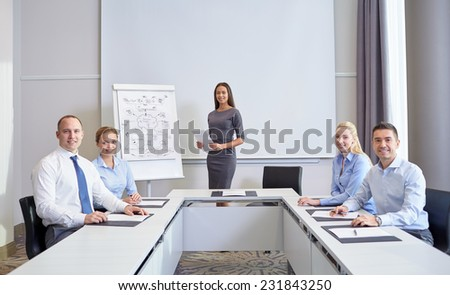 business, people and teamwork concept - group of smiling businesspeople meeting on presentation in office - stock photo