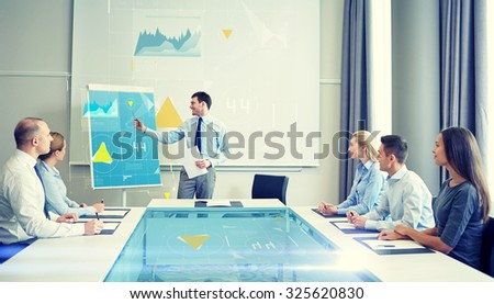 business, people and teamwork concept - group of smiling businesspeople with virtual charts projection meeting on presentation in office - stock photo
