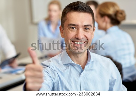 business, people and teamwork concept - smiling businessman showing thumbs up with group of businesspeople meeting in office - stock photo