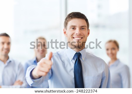 business, people and teamwork concept - smiling businessman showing thumbs up with group of businesspeople in office - stock photo