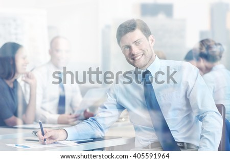 business, people and teamwork concept - smiling businessman with group of businesspeople meeting in office - stock photo