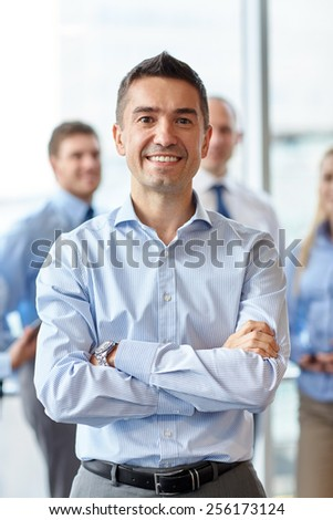 business, people and teamwork concept - smiling businessman with group of colleagues in office