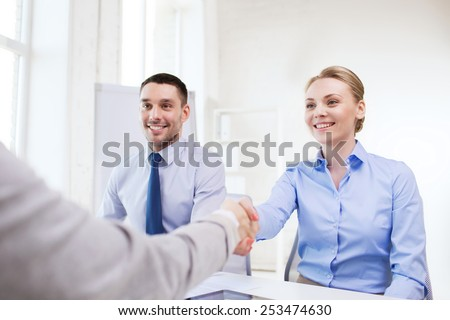 business, people and teamwork concept - smiling businesswoman making handshake gesture with group of businesspeople in office - stock photo