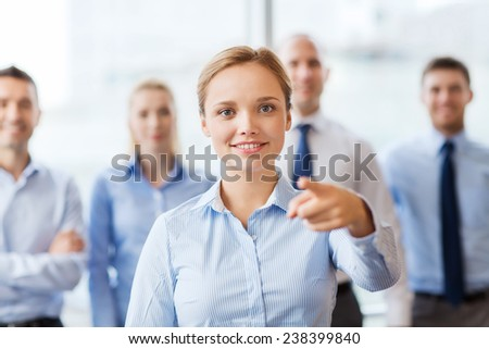 business, people and teamwork concept - smiling businesswoman pointing finger on you with group of businesspeople in office
