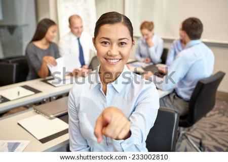 business, people and teamwork concept - smiling businesswoman pointing finger up with group of businesspeople meeting in office