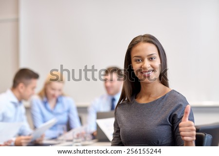 business, people and teamwork concept - smiling businesswoman showing thumbs up with group of businesspeople meeting in office - stock photo