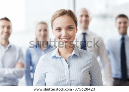 business, people and teamwork concept - smiling businesswoman with group of businesspeople in office