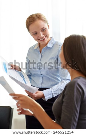 business, people and teamwork concept - smiling businesswomen with papers talking in office