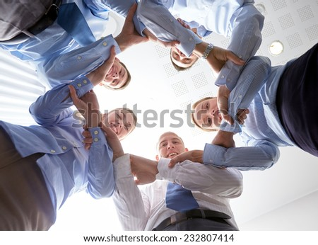 business, people and teamwork concept - smiling group of businesspeople standing in circle and holding to each other hands - stock photo