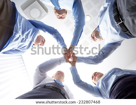 business, people and teamwork concept - smiling group of businesspeople standing in circle and making high five gesture - stock photo