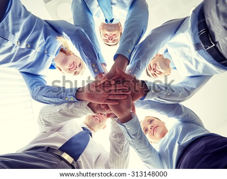 business, people and teamwork concept - smiling group of businesspeople standing in circle and putting hands on top of each other
