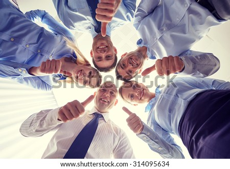 business, people and teamwork concept - smiling group of businesspeople standing in circle and showing thumbs up gesture - stock photo