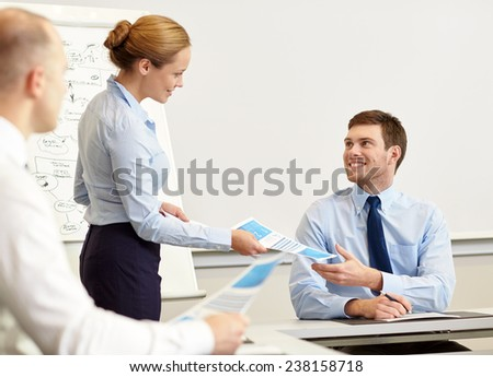 business, people and teamwork concept - smiling woman giving papers to man in office - stock photo