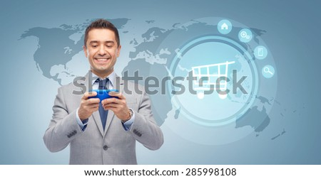 business, people and technology concept - happy businessman texting or reading message on smartphone over blue world map and shopping trolley background - stock photo