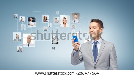 business, people and technology concept - happy businessman texting or reading message on smartphone over blue world map and network contacts background