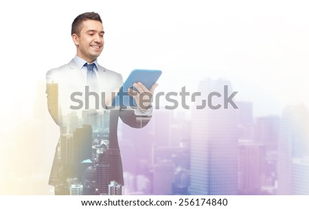 business, people and technology concept - happy smiling businessman in suit holding tablet pc computer over city background with double exposure - stock photo