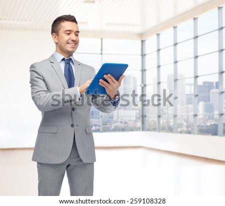 business, people and technology concept - happy smiling businessman in suit holding tablet pc computer over office room and window with city view background - stock photo