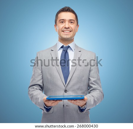 business, people and technology concept - happy smiling businessman in suit holding tablet pc computer over blue background - stock photo