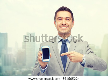 business, people and technology concept - happy smiling businessman in suit showing smartphone black blank screen over city background - stock photo