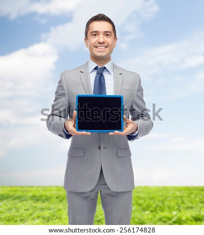 business, people and technology concept - happy smiling businessman in suit showing tablet pc computer black blank screen over blue sky and grass background - stock photo