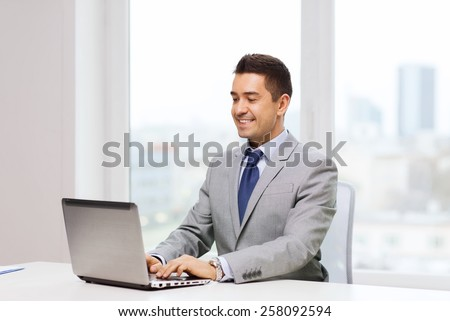 business, people and technology concept - happy smiling businessman in suit working with laptop computer in office