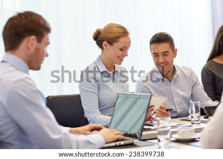 business, people and technology concept - smiling business team with laptop and tablet pc computer meeting in office - stock photo