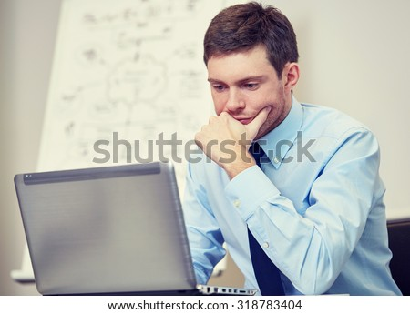 business, people and work concept - businessman sitting with laptop computer in office in front of whiteboard - stock photo