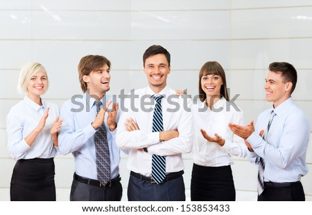 Business people applauding congratulating colleague, boss, team leader success, businesspeople group smile, at modern office