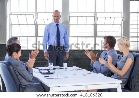 Business people applauding during meeting against inside a building