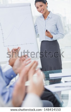 Business people applauding their cheerful colleague for her presentation in bright office - stock photo