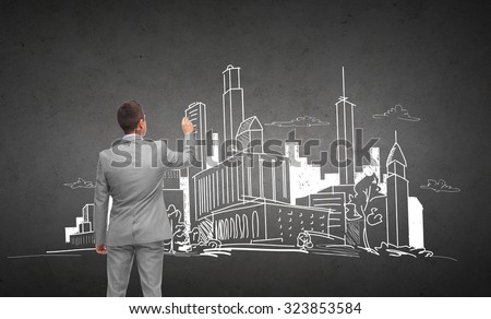 business, people, architecture and real estate concept - businessman drawing city sketch from back over dark gray concrete wall background - stock photo