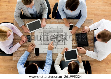 business, people, architecture and team work concept - close up of architects team with blueprint, smartphones and tablet pc computers sitting at table in office