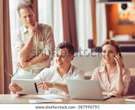 Business people are discussing business affairs, using laptop and tablet and smiling while working at the restaurant. Woman is talking on the mobile phone