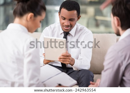 Business people are meeting in office to discuss project, are using tablet. - stock photo