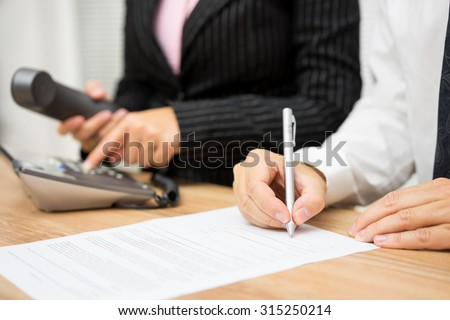 Business people are occupied with calling client or candidate and editing interview documents - stock photo