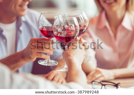 Business people are smiling, talking and clanging glasses of wine together during business lunch, close-up