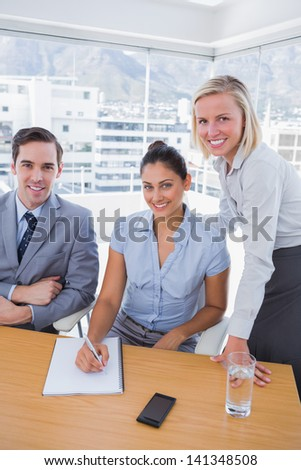 Business people at desk with notepad smiling at camera in the office