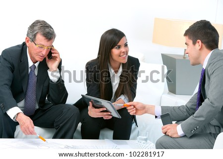 Business people at financial meeting with architectural plans on table.