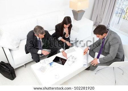 Business people at financial meeting with documents and tablet on table.
